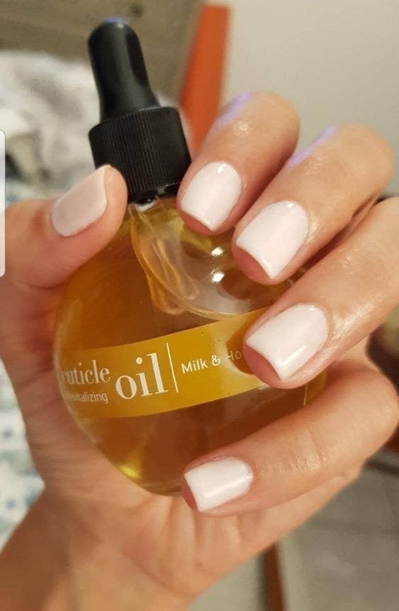 A reviewer holding the bottle with soft, painted nails