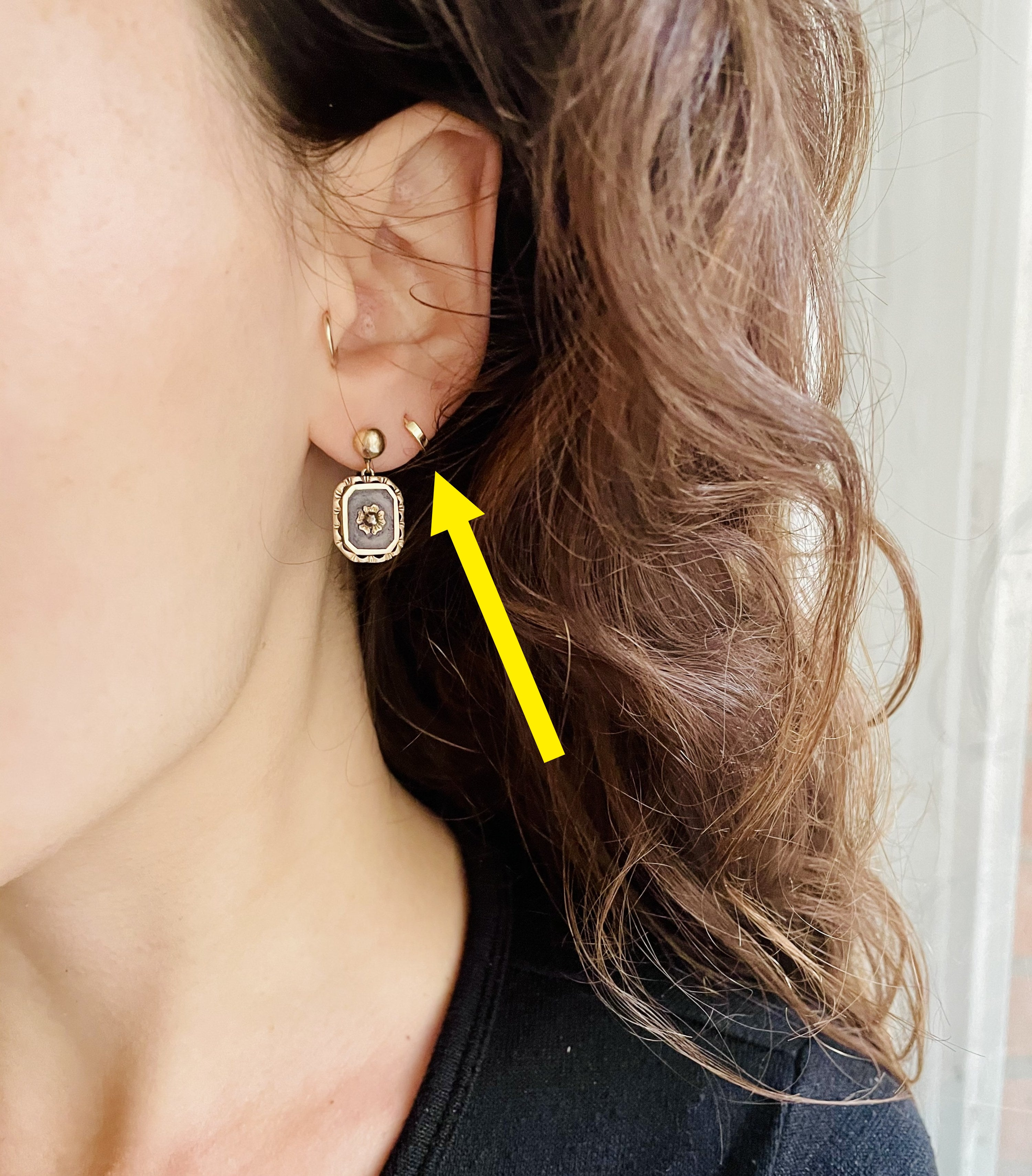 Brittany wearing earrings with an arrow pointing to the etsy hoops