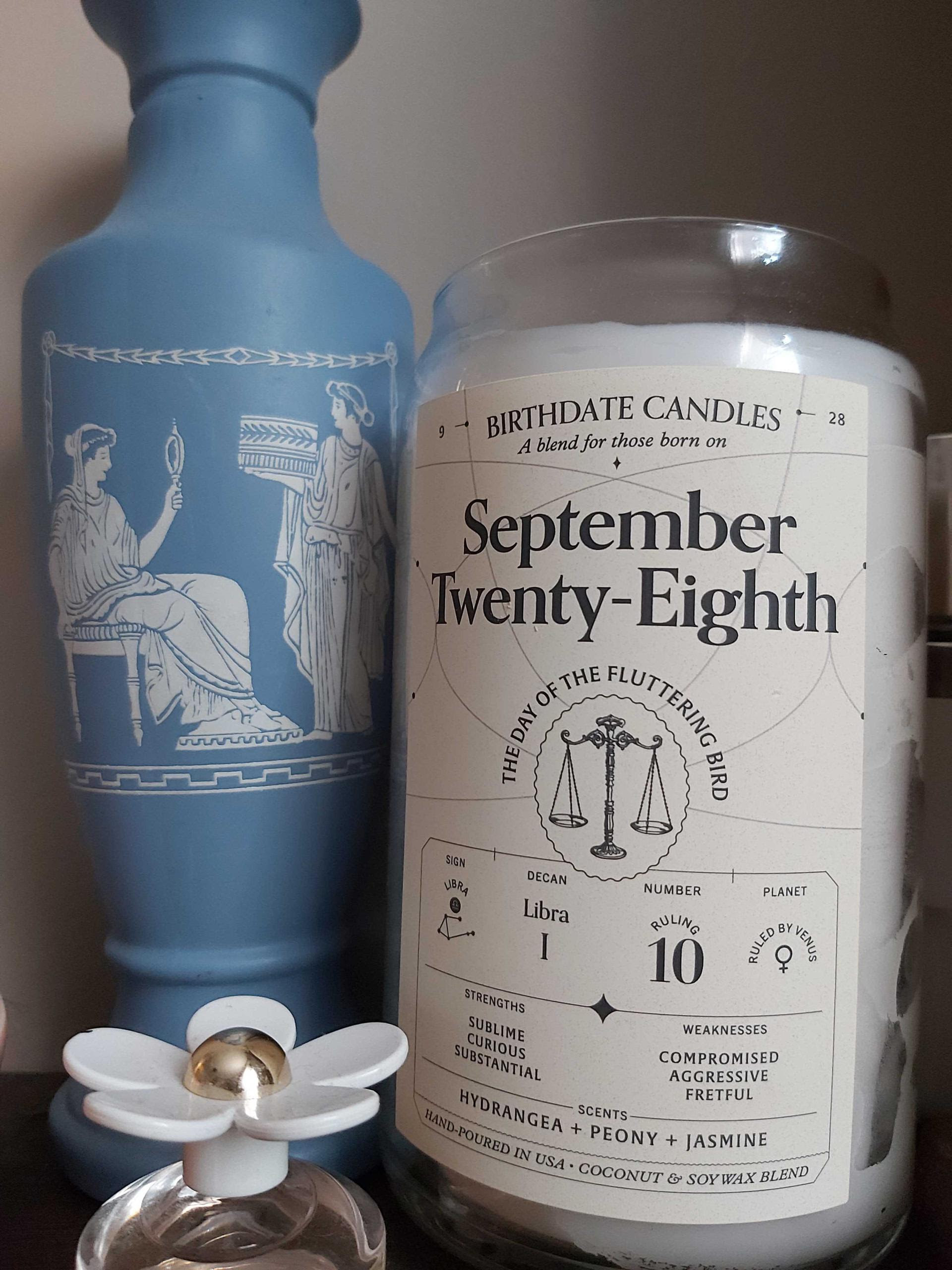 """buzzfeeder's candle in a jar that says """"september twenty-eighth, the day of the fluttering candle"""" with small astrological sign details for that date"""
