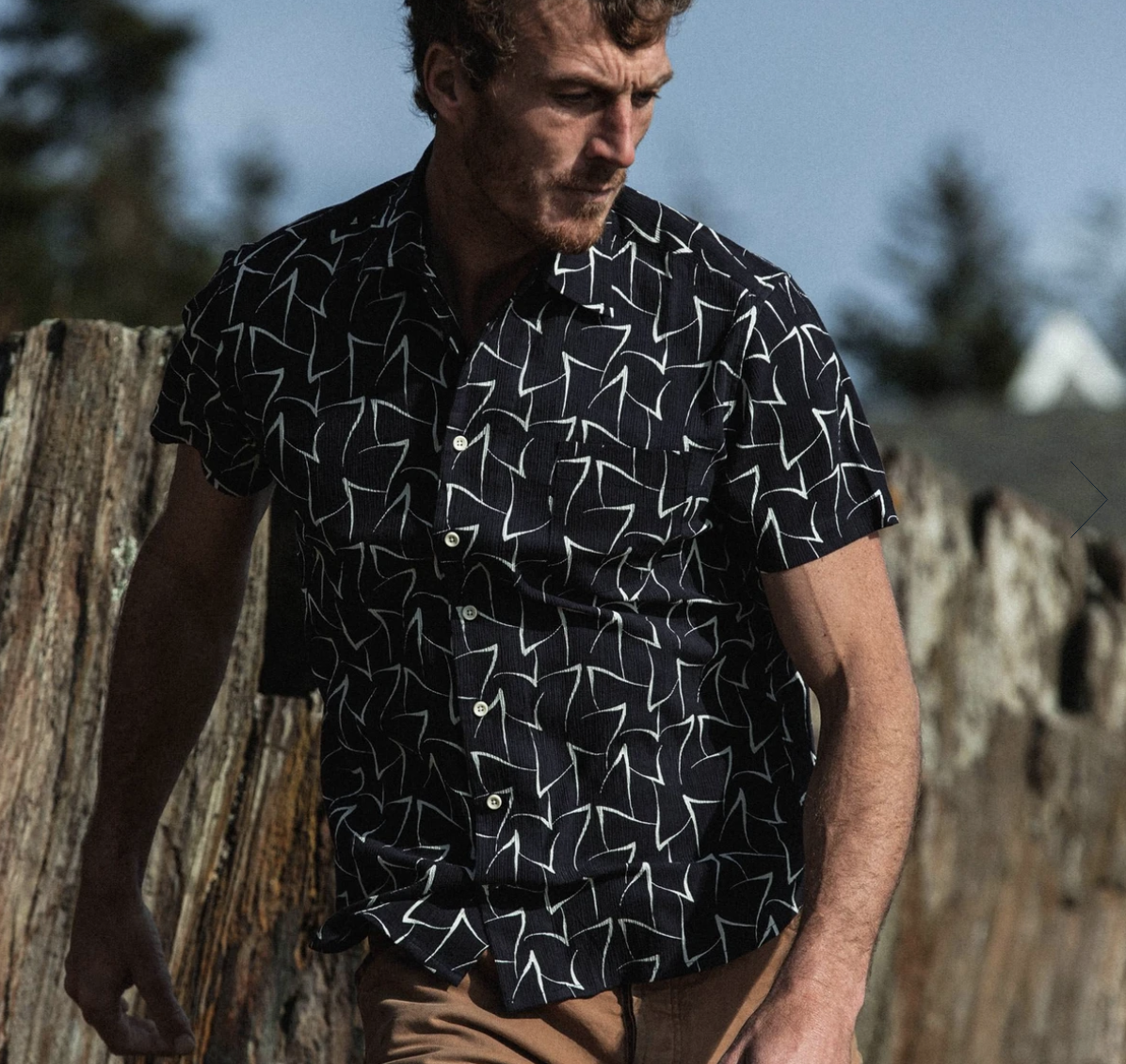 Model in navy blue collared short sleeved button down with white triangle pattern