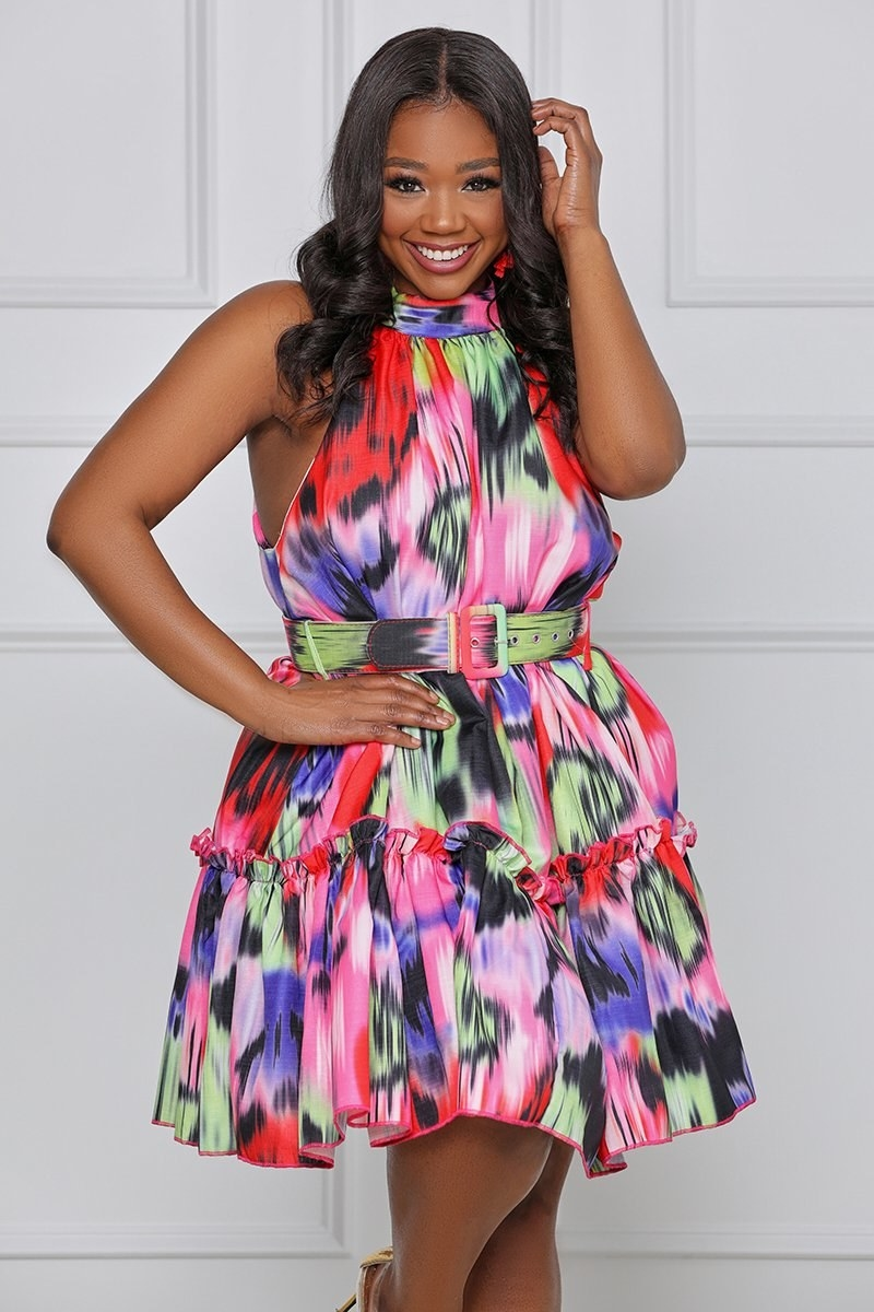 model wearing the pink, green, black, purple, and red print belted halter dress