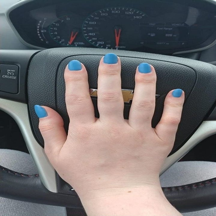 Reviewer showing off nails with a blue color