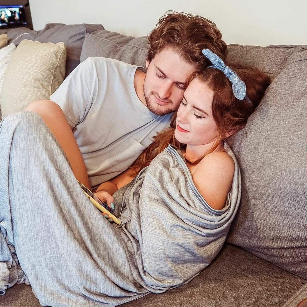 Two models snuggled under the blanket on a couch