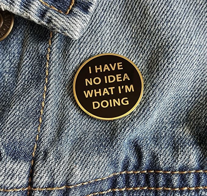 """a black circle pin with a gold edge that says """"i have no idea what I'm doing"""" in gold"""
