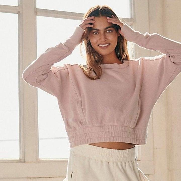 a model wearing the sweatshirt in light purple
