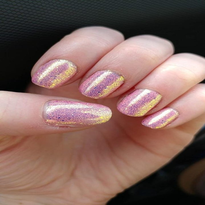 Reviewer showing off nails with a glittery pink color