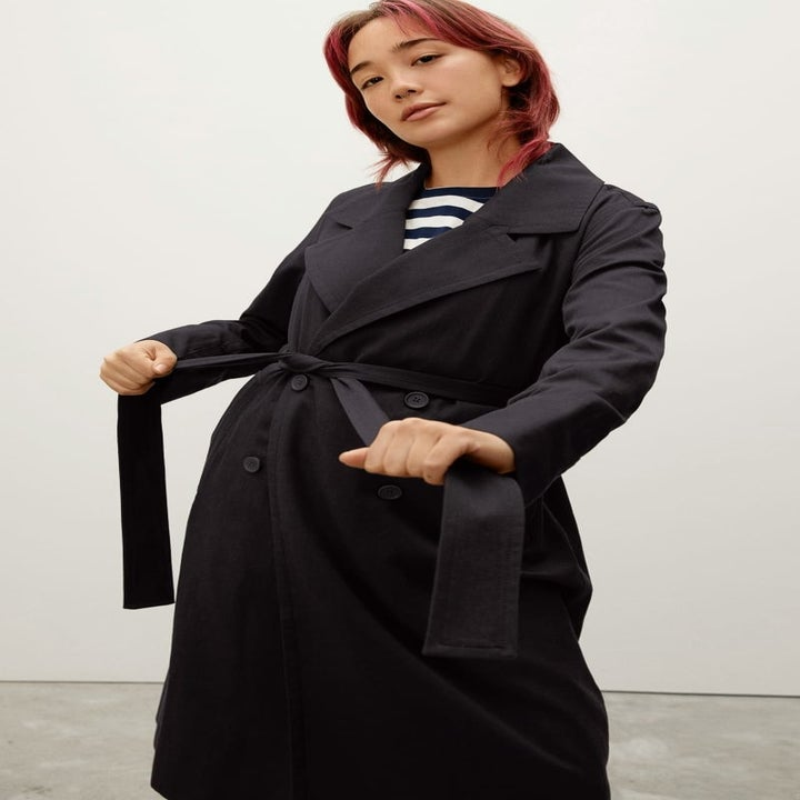model wearing the black trench closed, cinching it with the waist tie