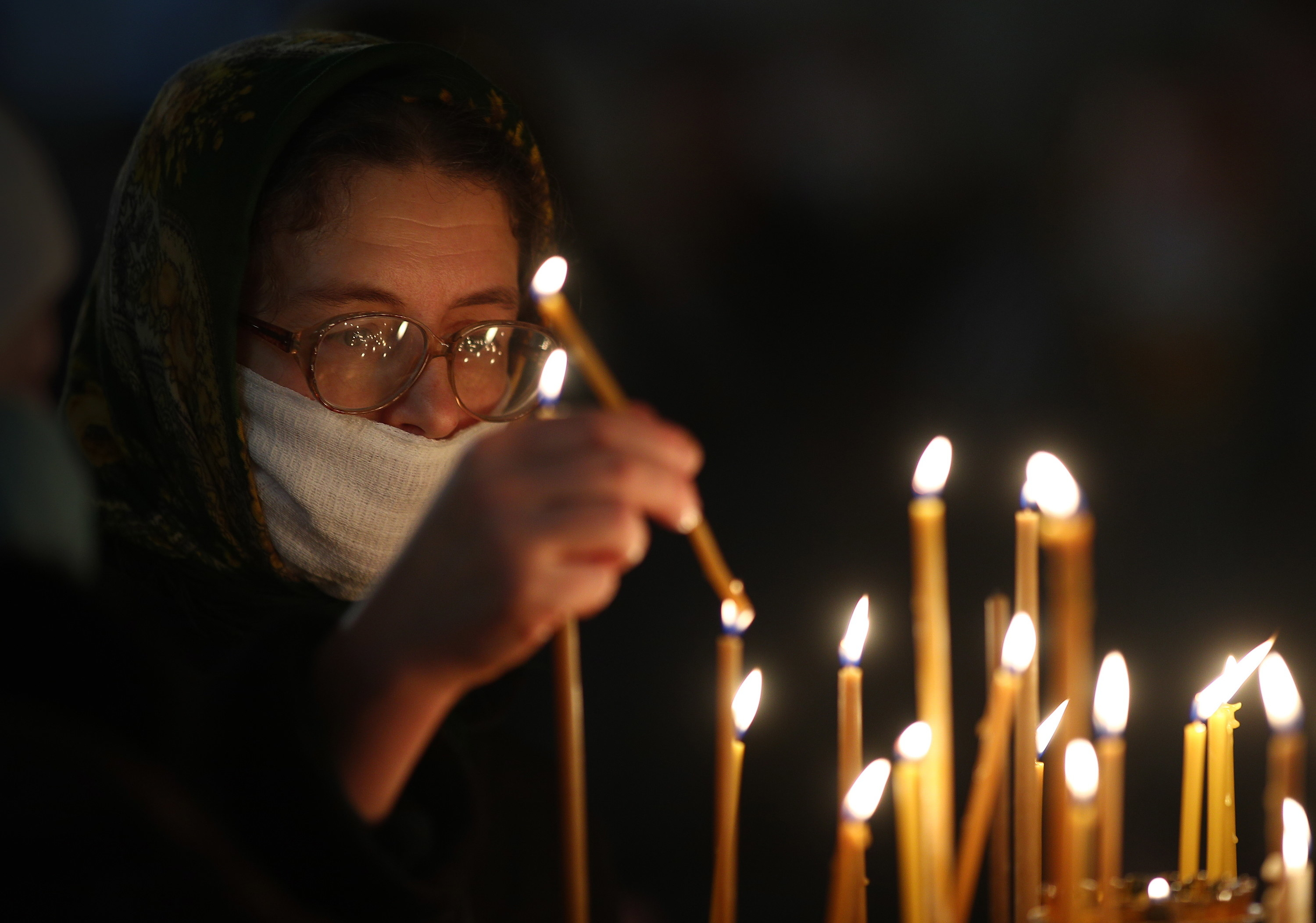 A woman in a face mask lighting candles in a church