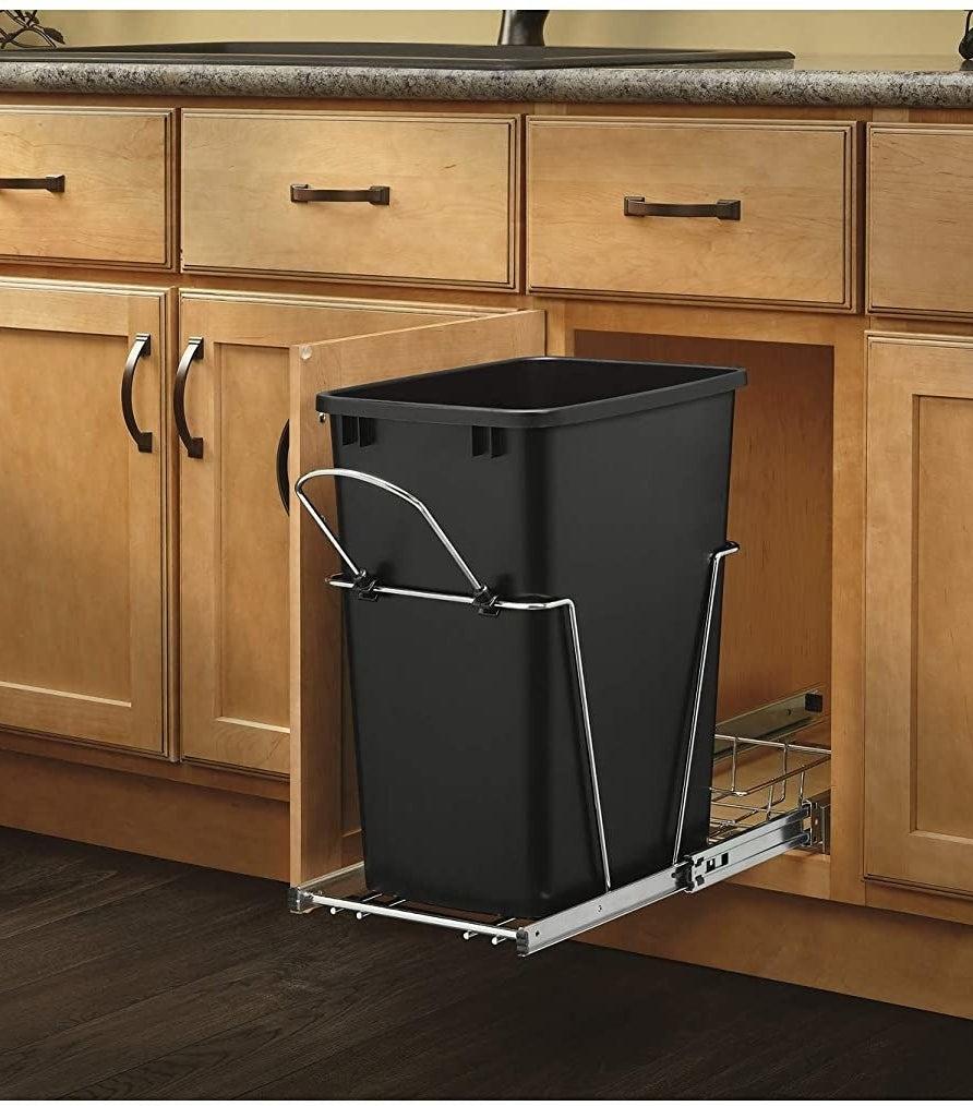 black trash can on metal track sliding out of cabinet