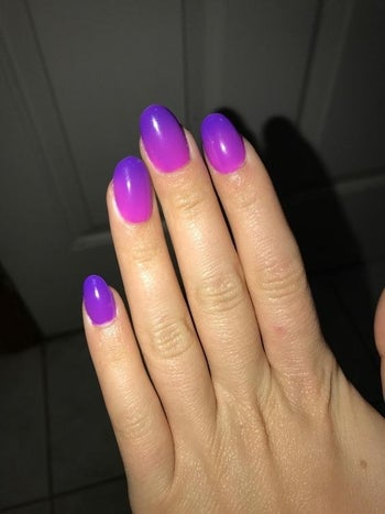 Reviewer showing off purple painted nails with no chips or smudges