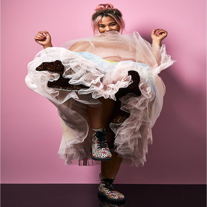 Model wearing the spaghetti-strap dress and kicking one leg up so you can see the layers of pink, blue, and yellow tulle and the leopard lining
