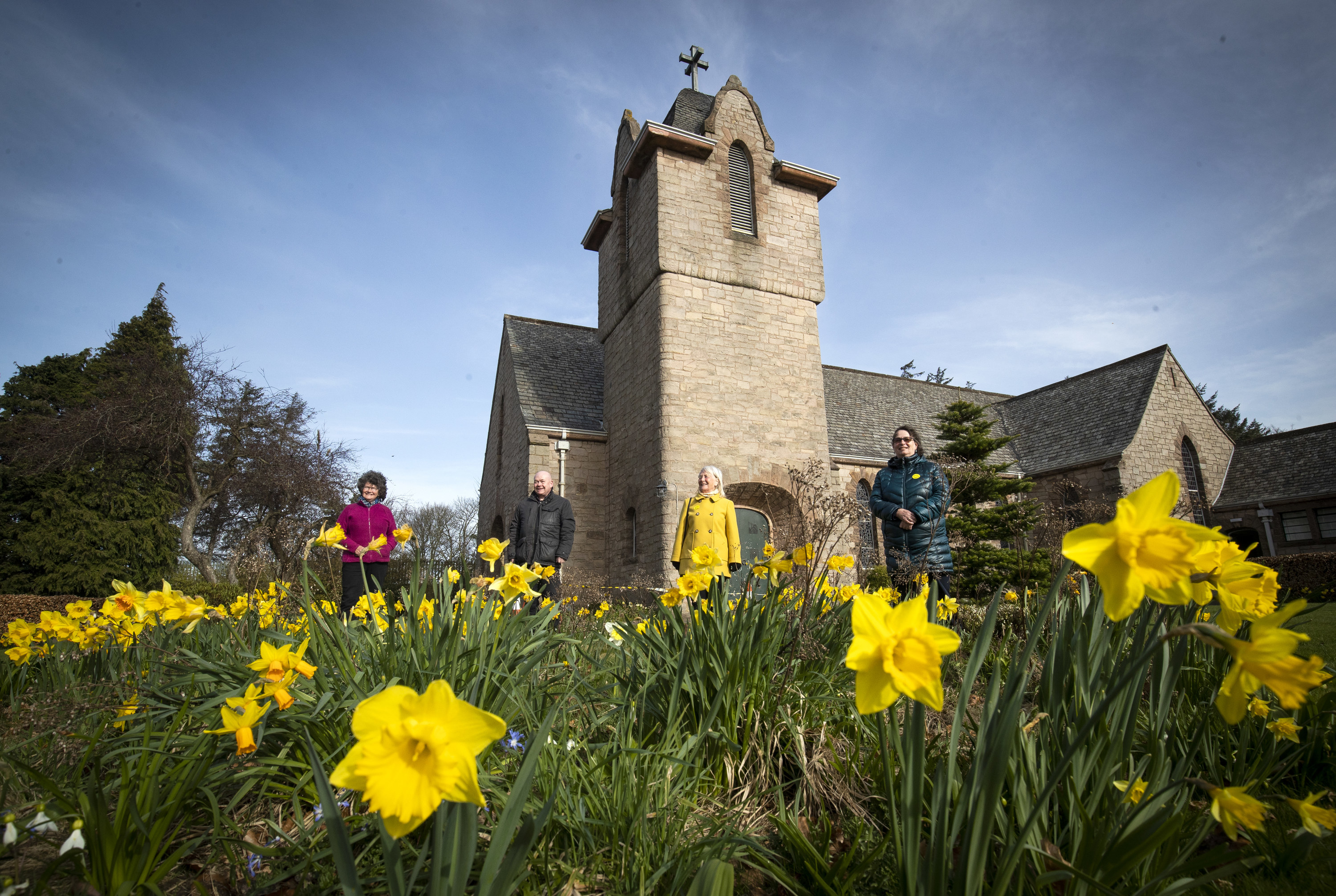 People standing outside of a church with daffodils in full bloom