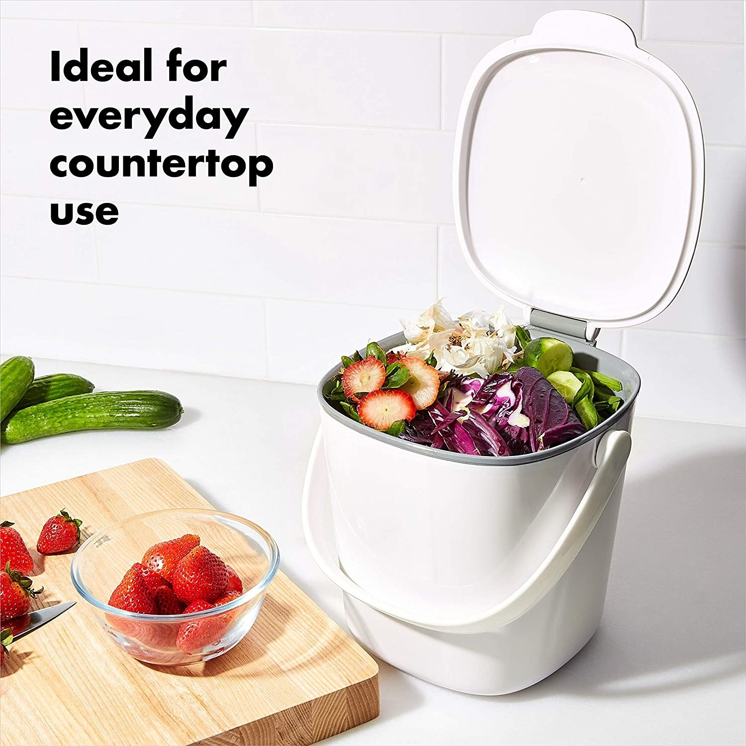 white compost bin with lid open, filled with vegetable scraps