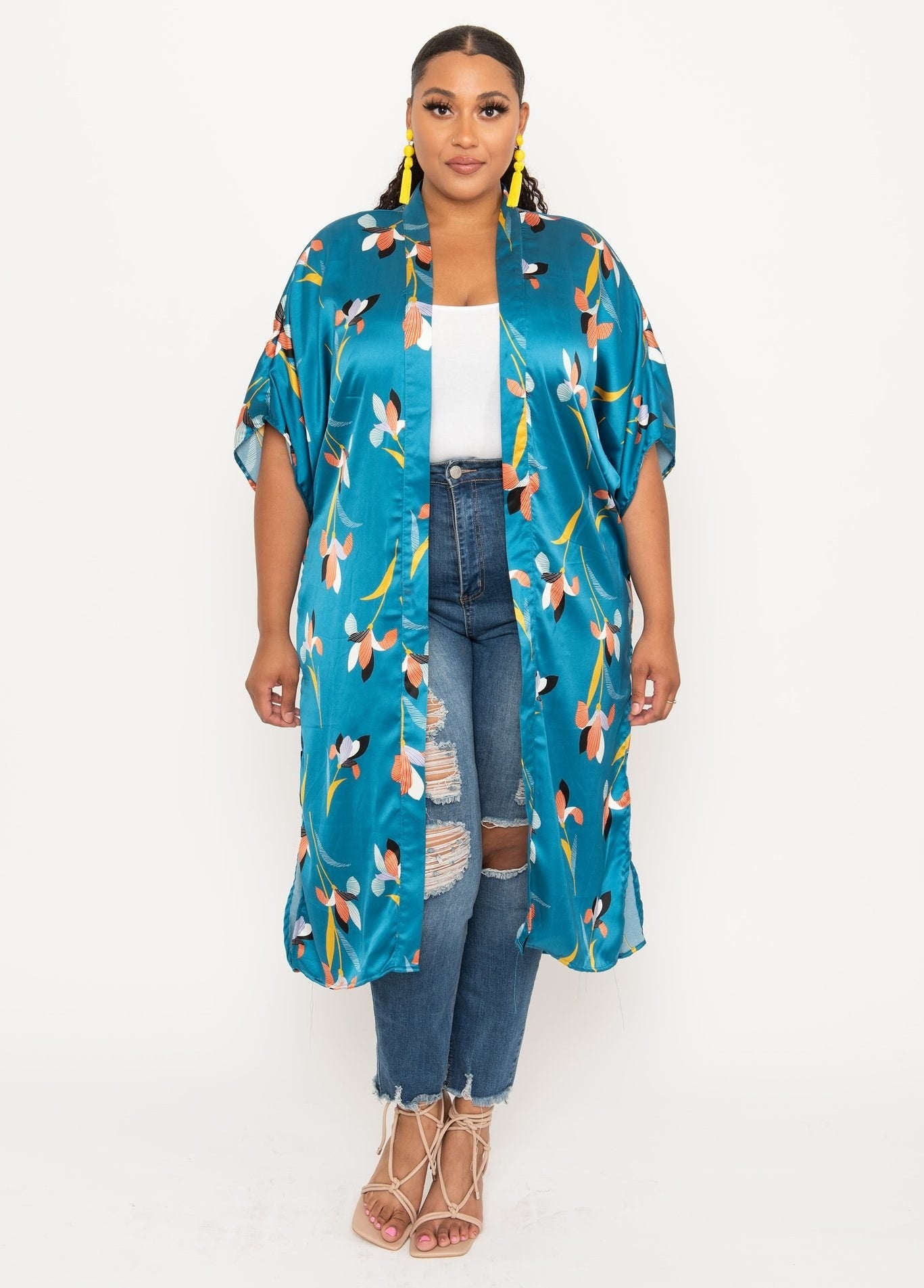 a model wearing jeans, a white t-shirt and a printed silky duster that goes below the knees