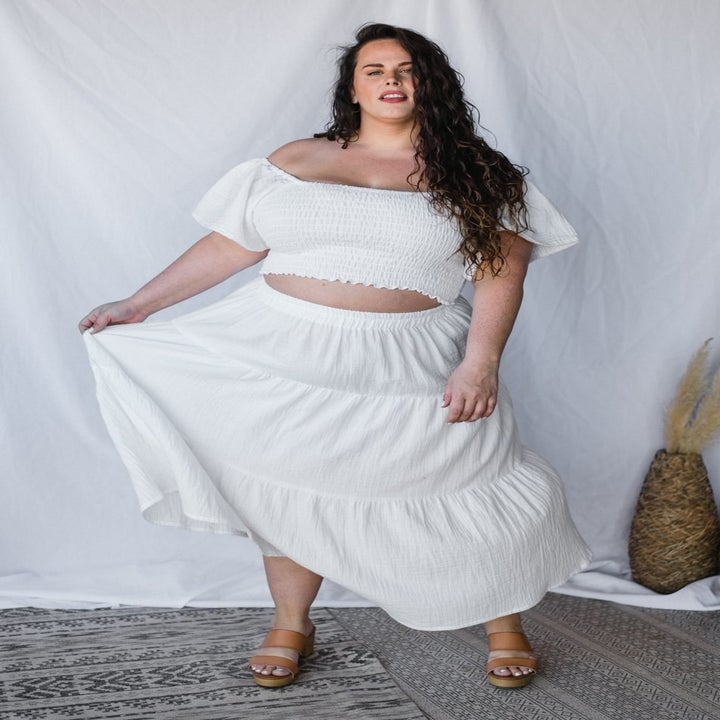 a model wearing a crop top and the midi skirt in white