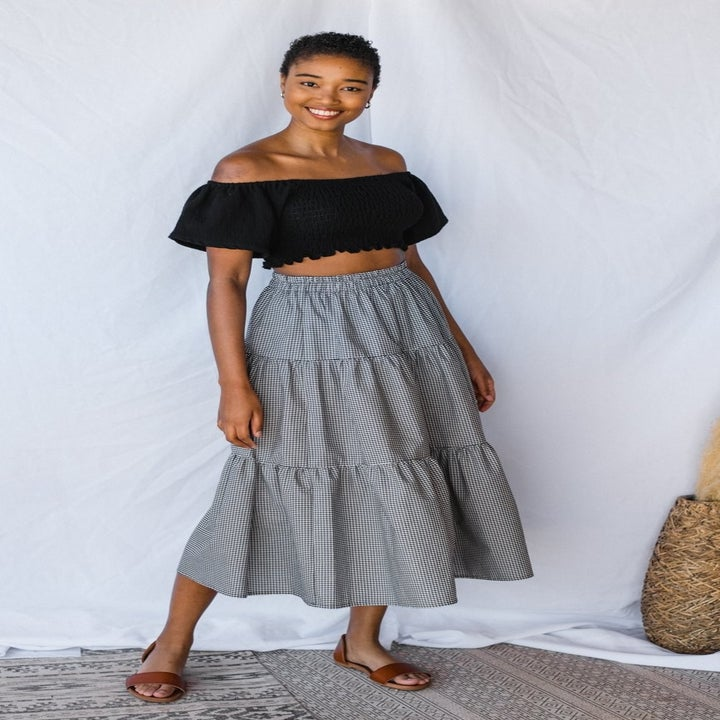 a model wearing a black cropped top and the tiered midi skirt in a black and white gingham print