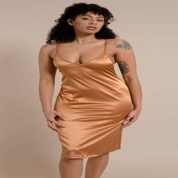 a model wearing the same slip dress in a caramel color
