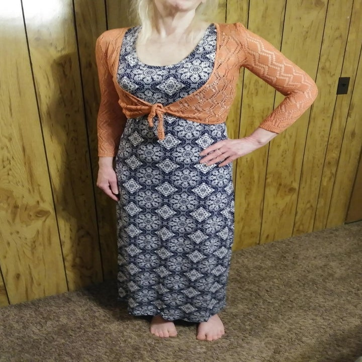 a reviewer wearing the tank dress with a navy and white print underneath an orange cardigan tied in the front