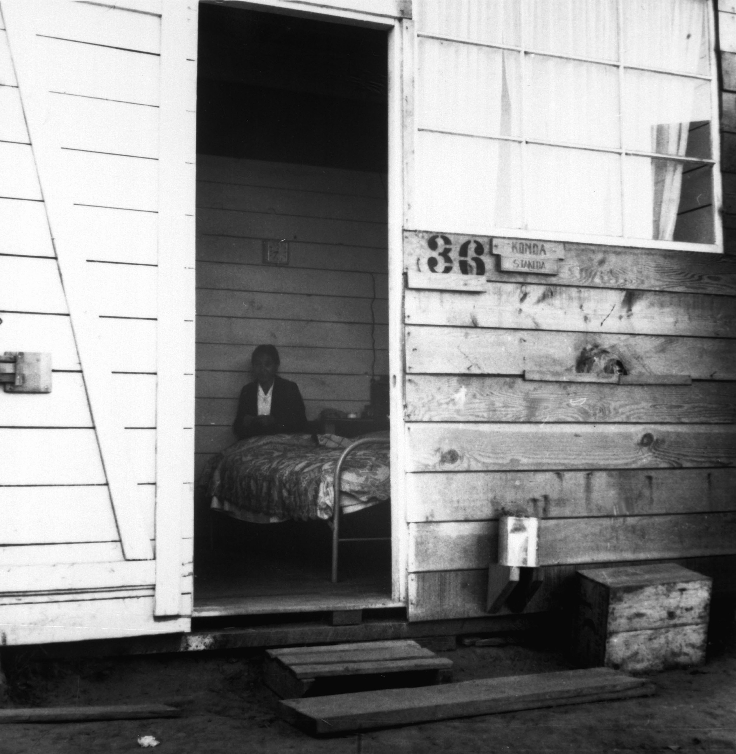 The unit's open door shows a woman sitting next to a bed