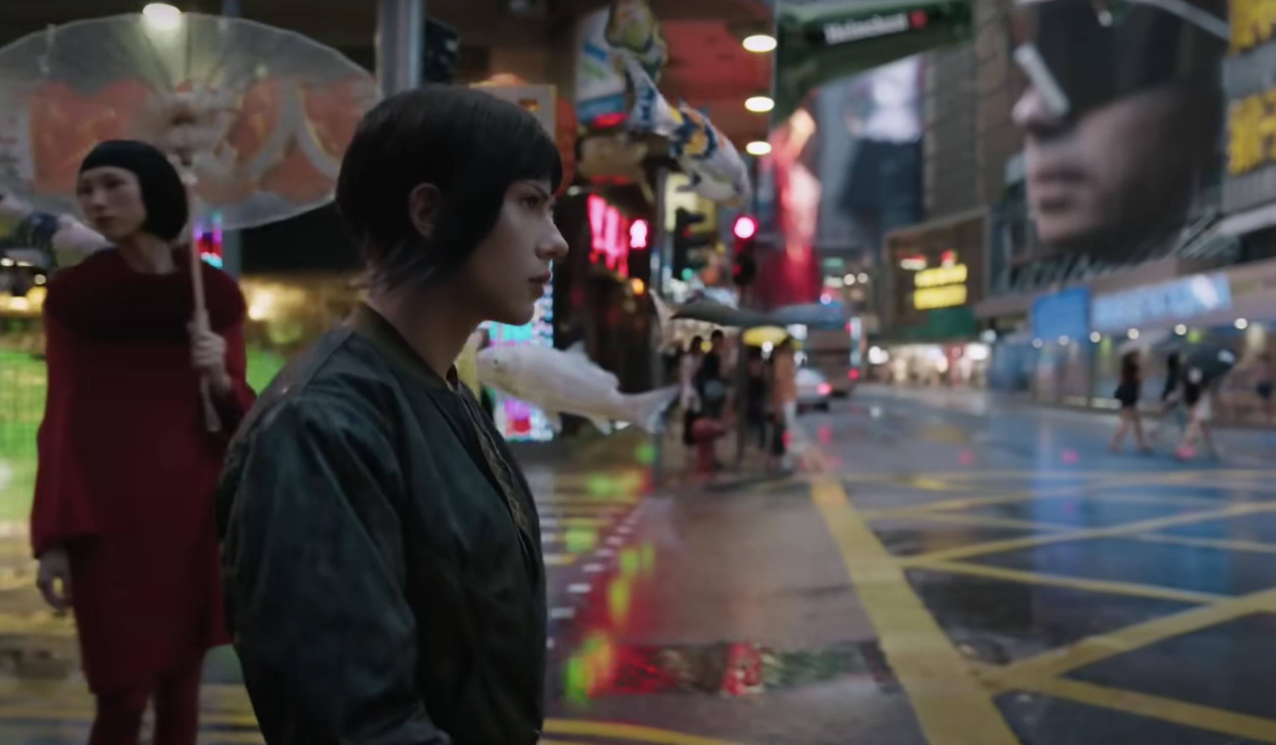 Scarlett Johansson's character walks past shops on a street in Japan