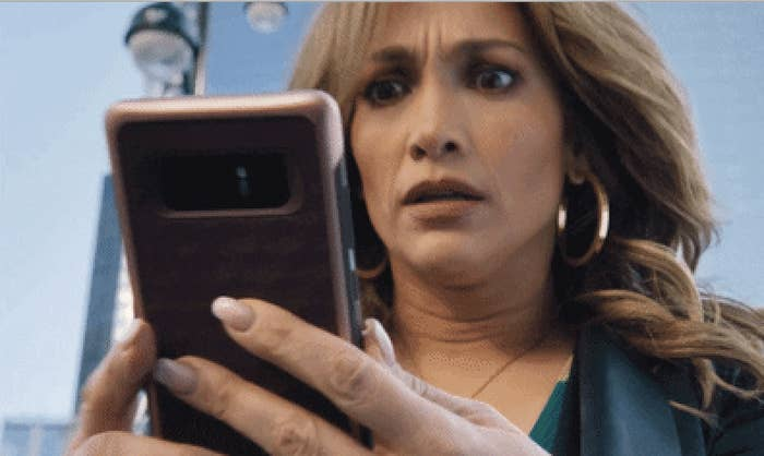 A woman stares at her phone with wide eyes
