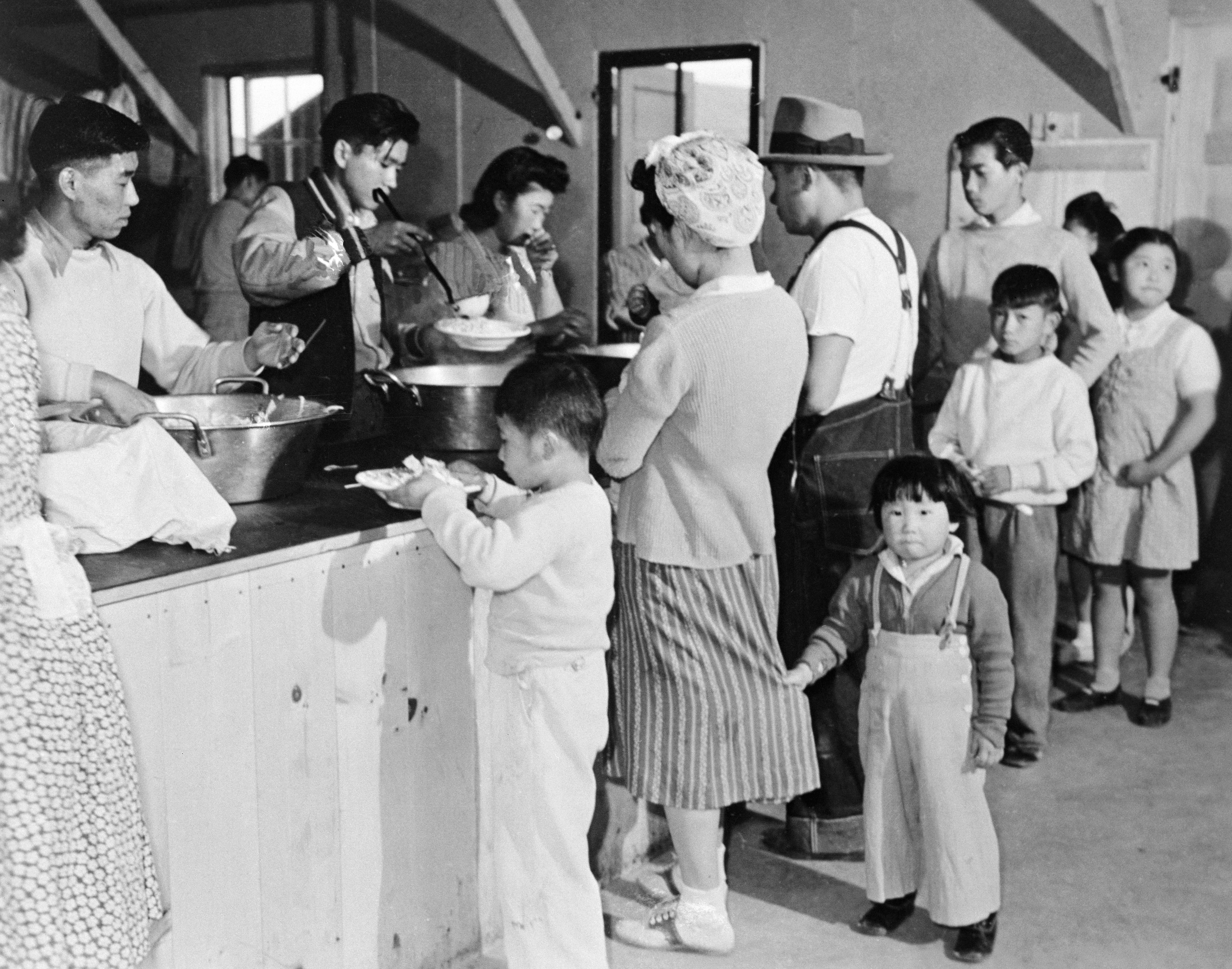 A little boy holding onto the skirt of a woman as she is served a plate of food