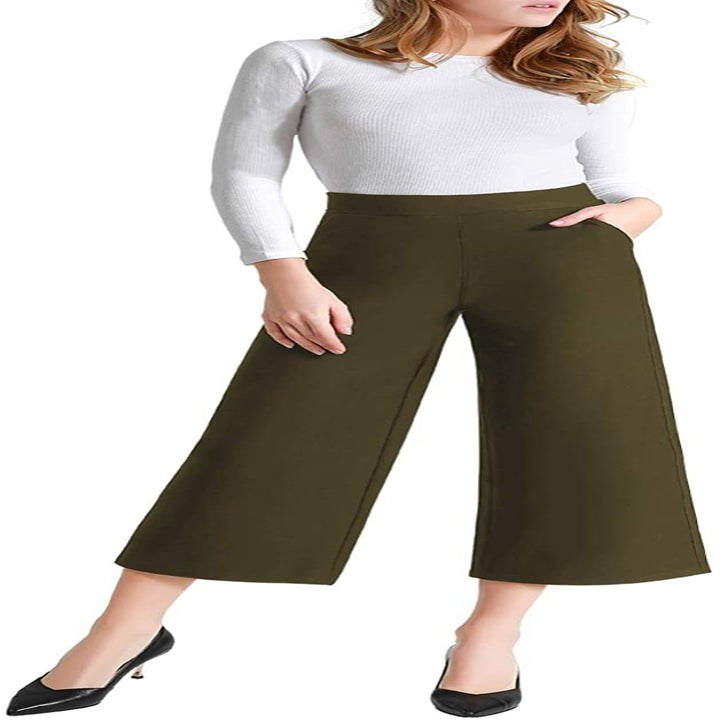 a model wearing the pants in khaki green with a white shirt tucked in