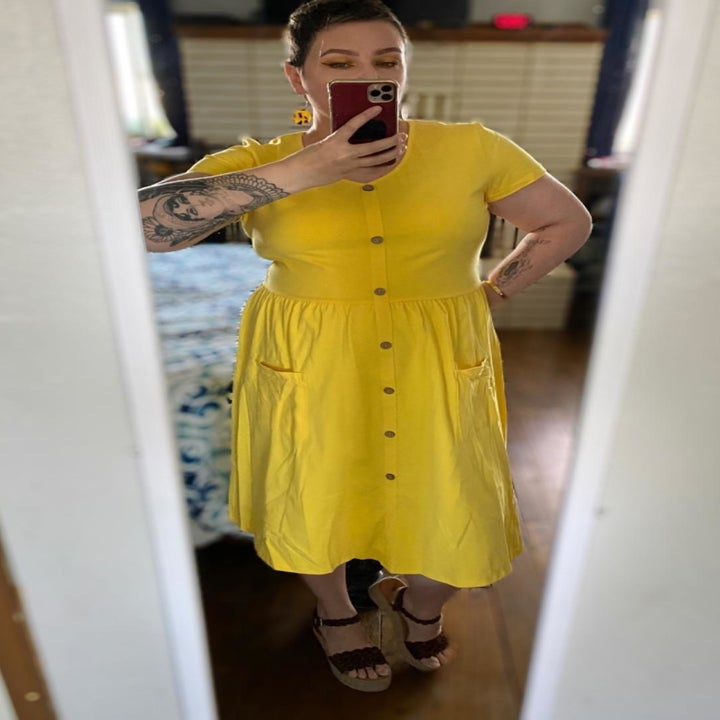 a reviewer mirror selfie of them wearing the yellow short-sleeved midi dress