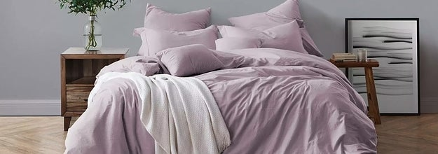 The cotton bedding set in dusty lavender next to two mismatched nightstand