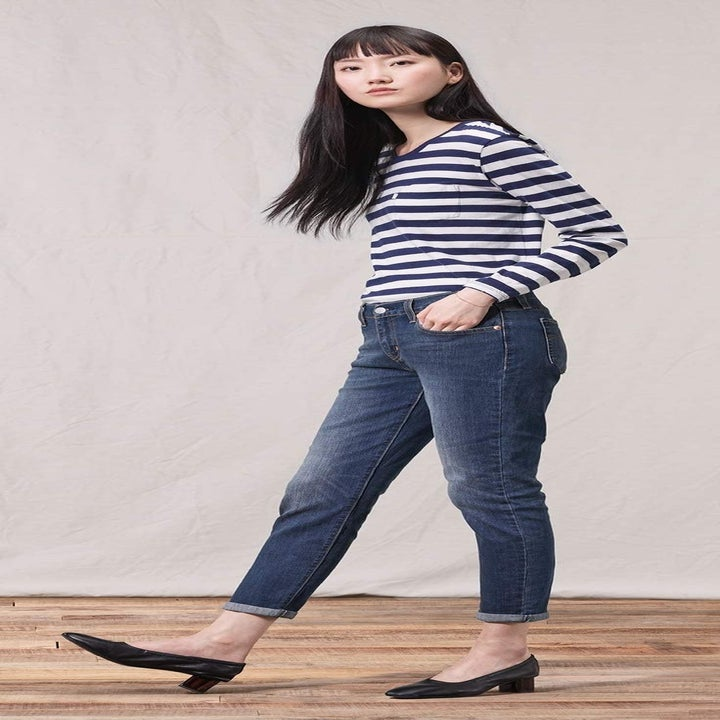 a model wearing a striped shirt and dark wash boyfriend jeans cuffed at the ankles