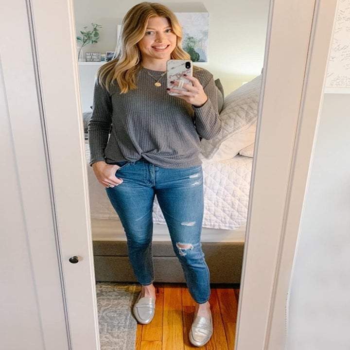 a reviewer mirror selfie of them wearing jeans and the light gray sweater with a knit detail at the hem