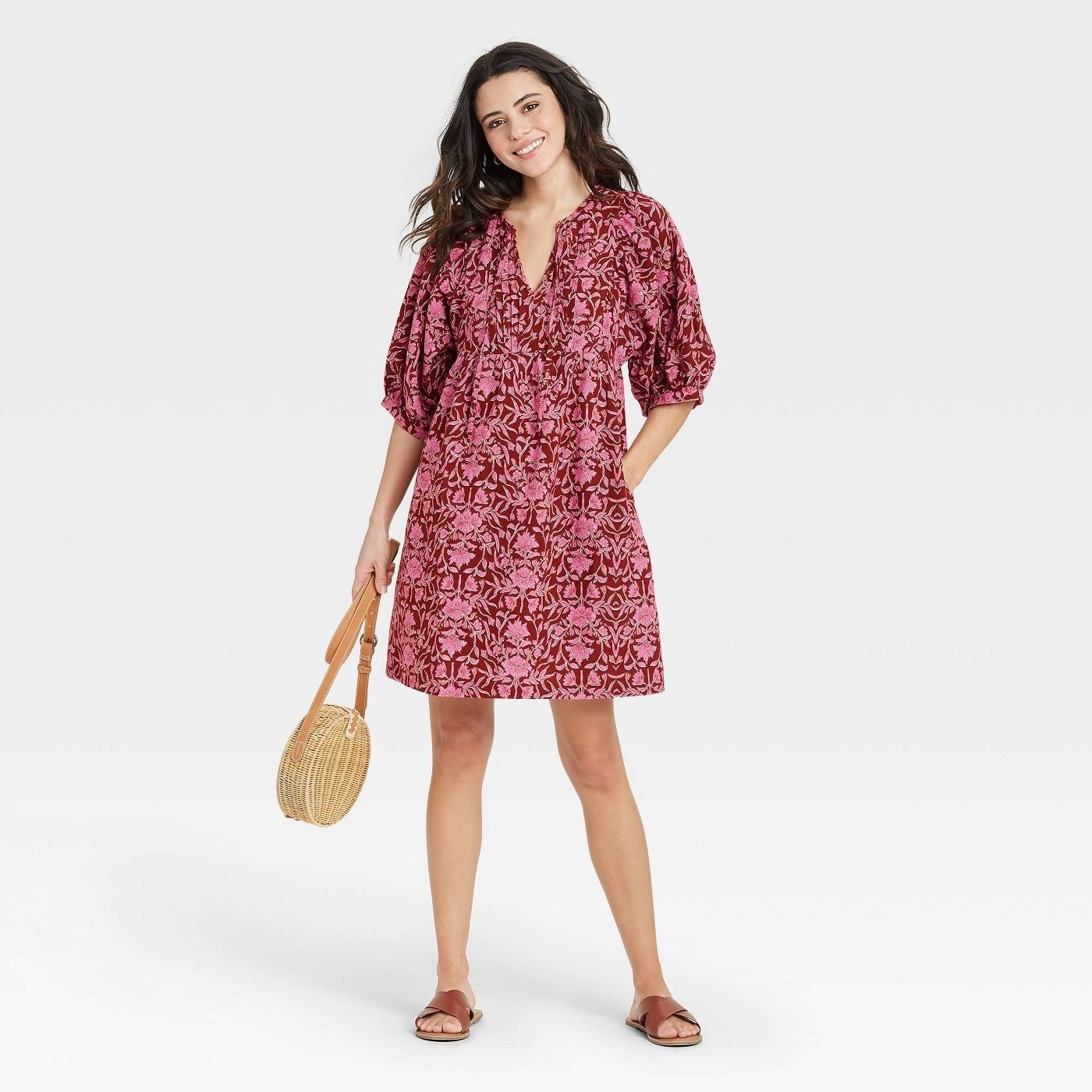 Model wearing pink floral dress with burgundy background, stops above the knee