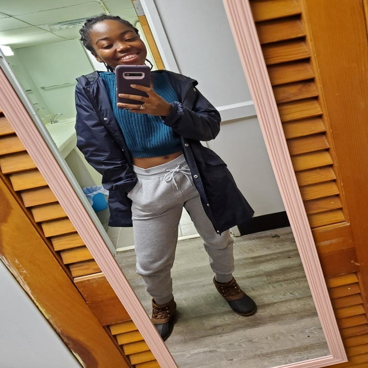 a reviewer mirror selfie of someone wearing the open navy raincoat