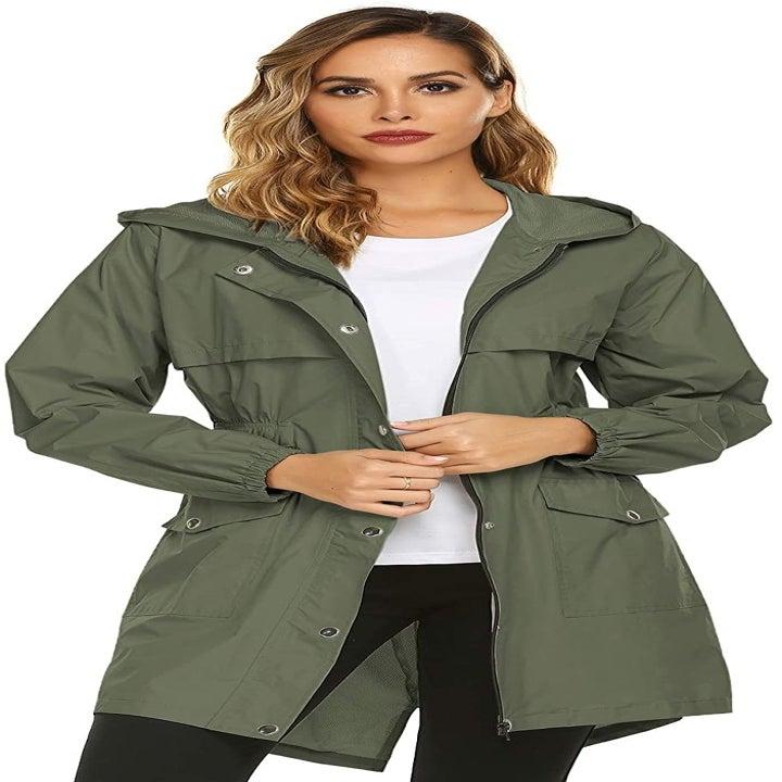 a model wearing the raincoat in khaki green