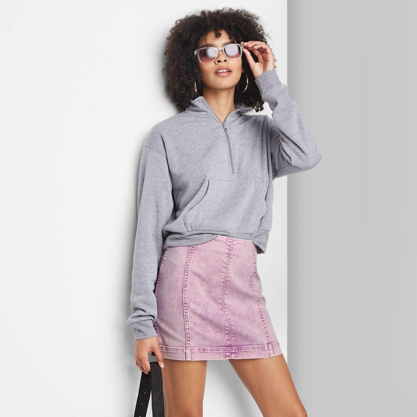Model wearing pink seamed denim skirt, stops mid thigh