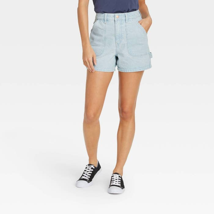 Model wearing light denim shorts with strap on right side