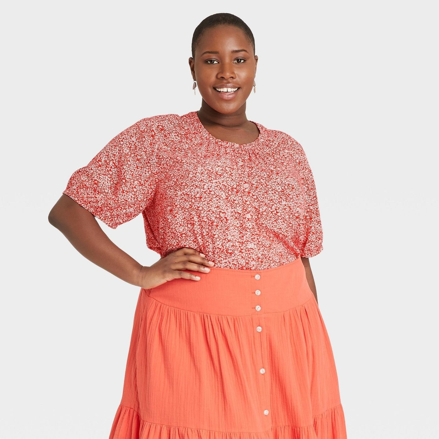 Model wearing orange button down blouse with round neck
