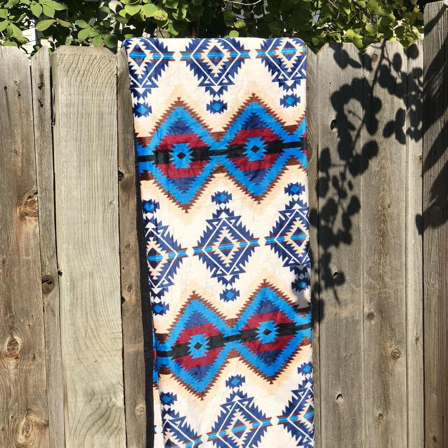 blue, white, tan, and red patterned blanket folded and hangin over a fence
