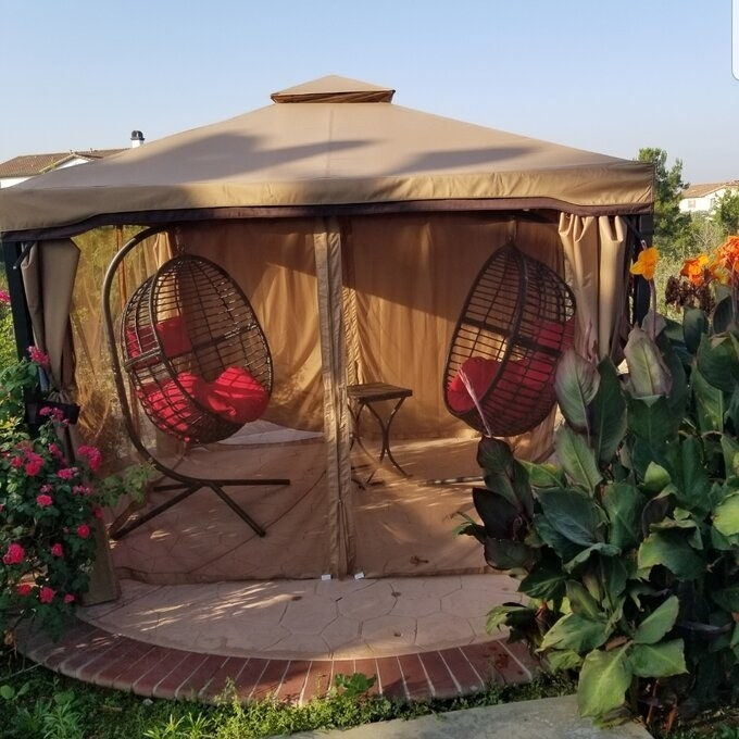a reviewer's gazebo with. two chairs and a table inside