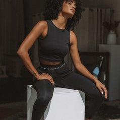 A woman sits on a plinth with her eyes closed in black activewear.