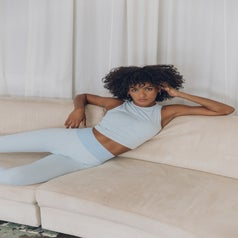 A woman lounges on a couch wearing pale blue activewear.