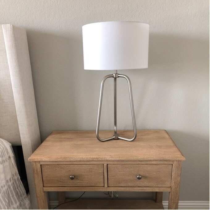 a reviewer's brushed nickeltable lamp on a nightstand