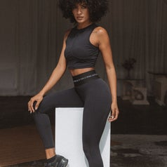 A woman sits on a plinth in activewear.