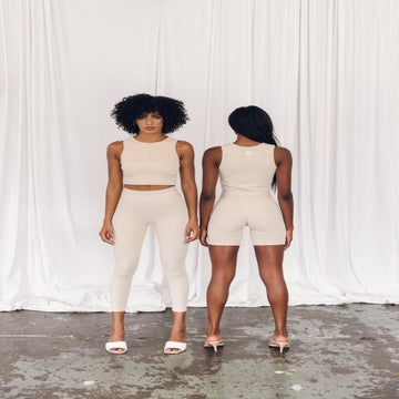 Two women pose in cream colour activewear.