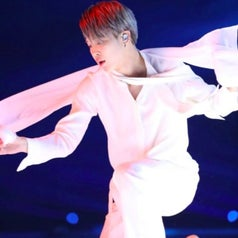 Jimin dances with a white piece of fabric, dressed all in white with silver hair