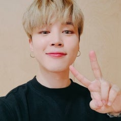 Jimin has blonde hair and smiles at the camera while doing a peace sign