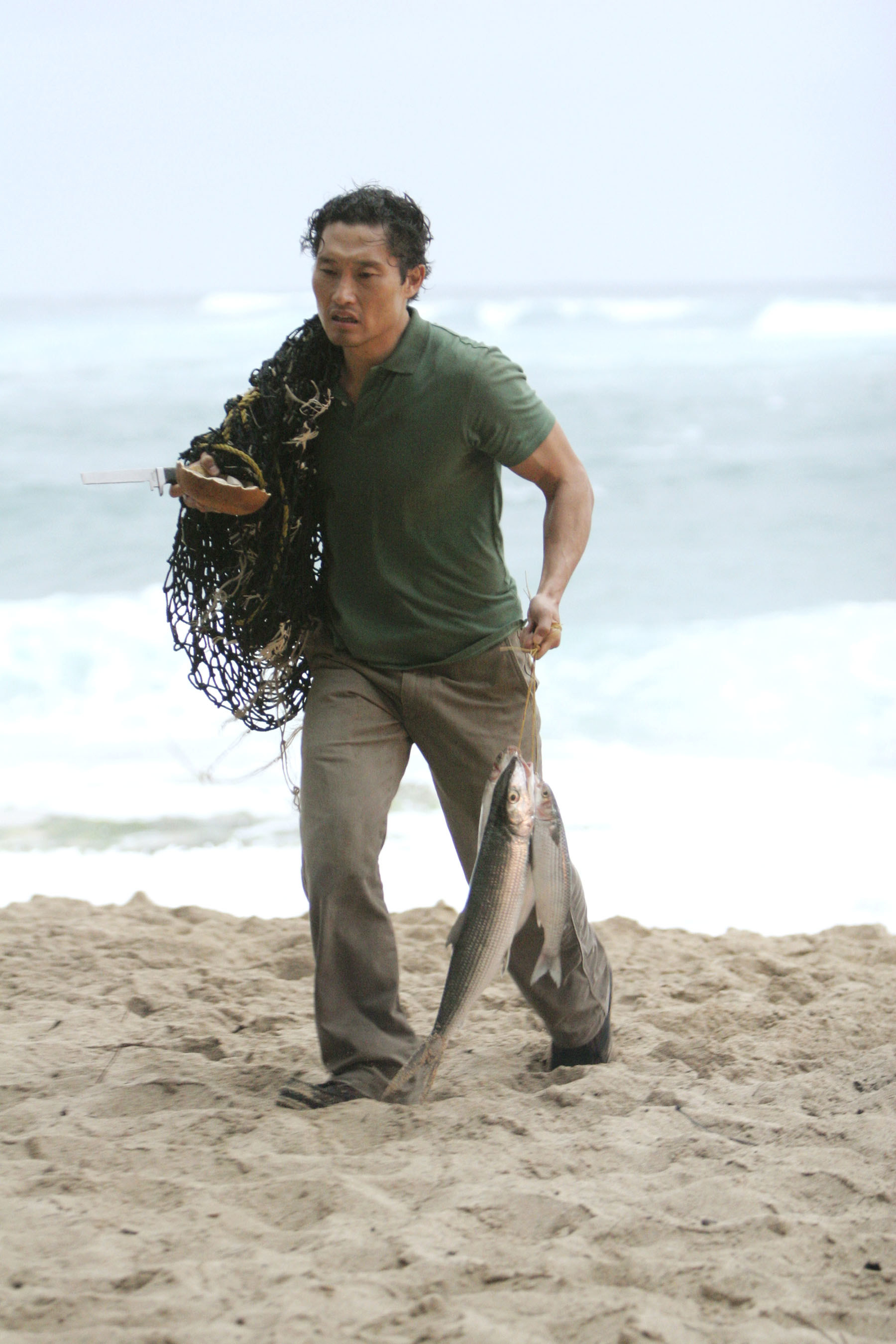 Kim carries a net and fish on the beach in the TV show Lost