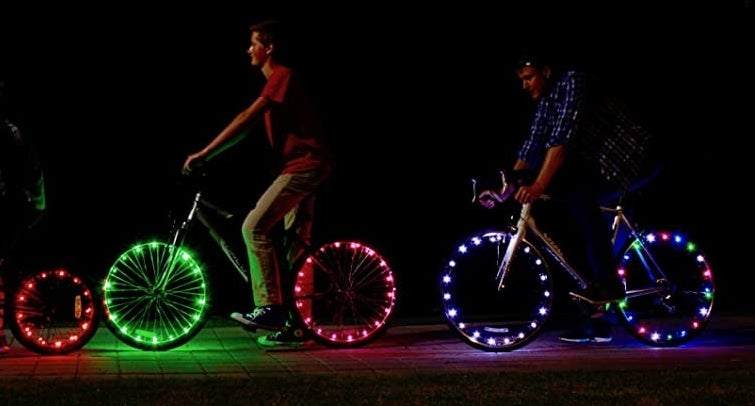 Two people riding bikes in the dark with bright lights on their wheels