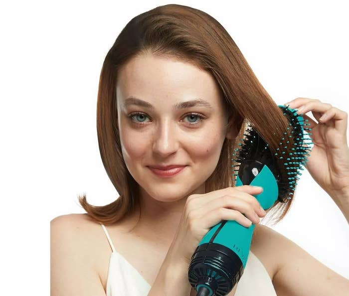 A model doing their hair with the hair dryer and volumizer