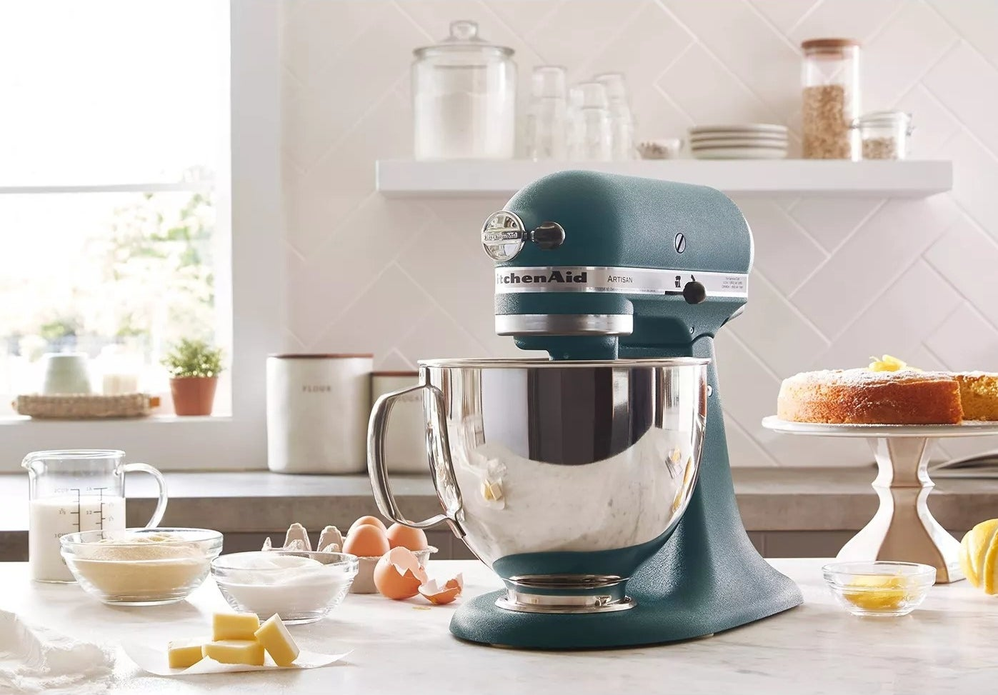 The pebbled hunter green stand mixer on a kitchen counter mixing dough